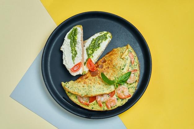 Continentaal ontbijt - omelet met garnalen, tomaten en basilicum met toast met roomkaas en pesto op een zwarte plaat op s.