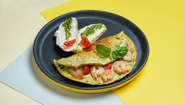 Continentaal ontbijt - omelet met garnalen, tomaten en basilicum met toast met roomkaas en pesto op een zwarte plaat s.