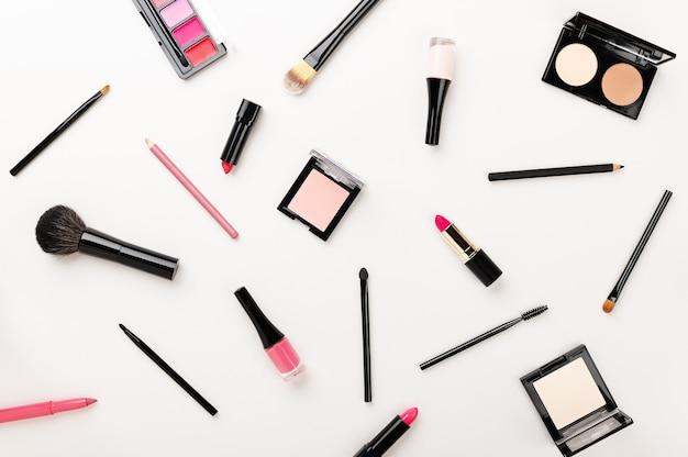 Contouren van poeder, markeerstift, blush, lippenstiftkit, make-upborstels, lippotlood, eyeliner op wit