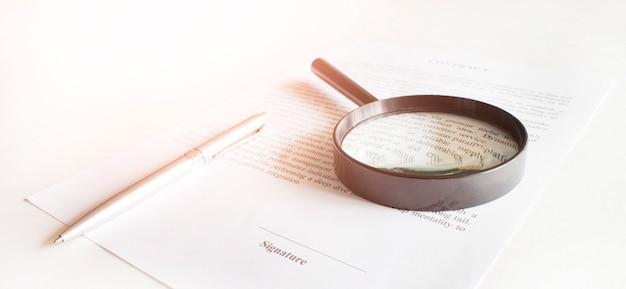Contract met pen en vergrootglas. bedrijfsconcept