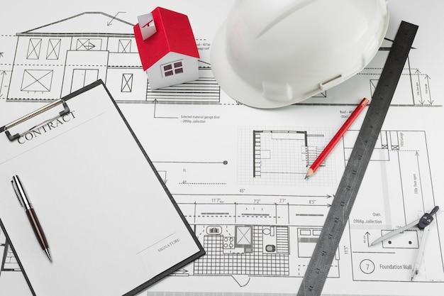 Contractdocument en huismodel met witte bouwvakker op blauwdruk