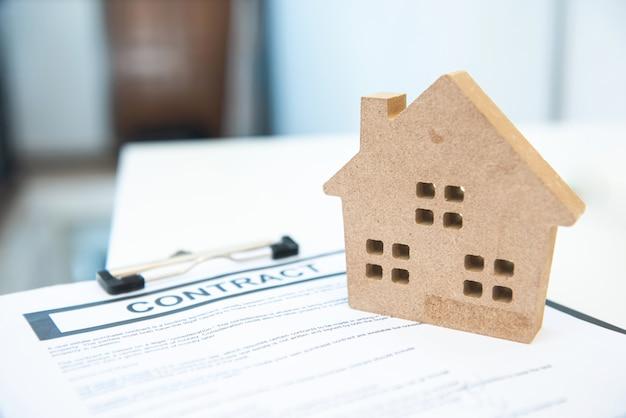 Contractteken met huisstuk speelgoed vorm, concept onroerende goederen en huisbezit.