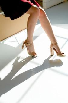 Contrasterende schaduw van vrouwelijke benen in schoenen onder fel zonlicht