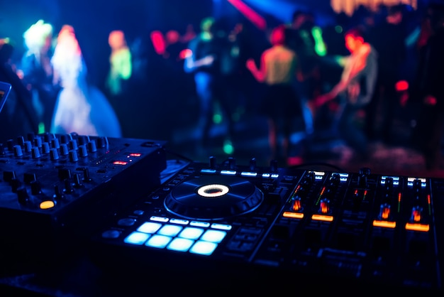 Controle dj voor het mixen van muziek met wazige mensen dansen op feestje in nachtclub