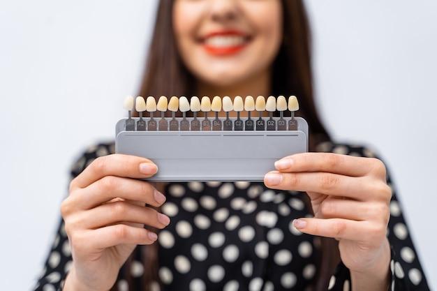 Controleer en selecteer de kleur van de tanden in de tandartspraktijk. proces van het kiezen van tandenkleur voor een mooi jong meisje.