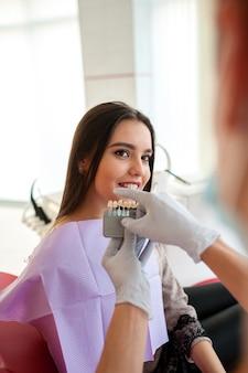 Controleer en selecteer de kleur van de tanden voor een mooi donkerbruin meisje.