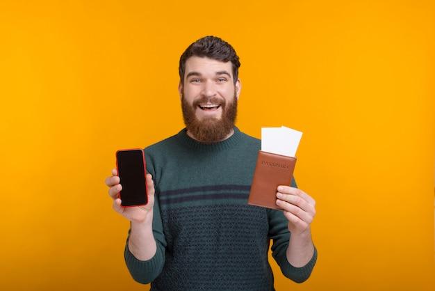 Controleer uw reisinformatie aan de telefoon. de knappe mens houdt een paspoort met kaartjes en een telefoon in zijn handen op gele ruimte.