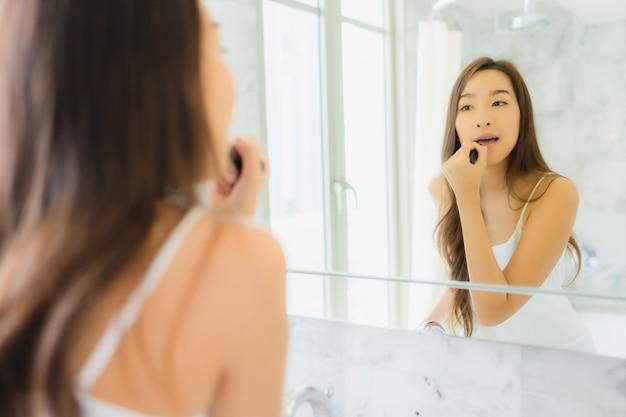 Controleert de portret mooie jonge aziatische vrouw en maakt omhoog haar gezicht