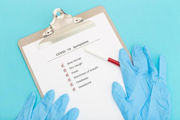 Controlelijst op klembord covid-19 symptomen concept. evaluatielijst covid-uitbraak. bovenaanzicht