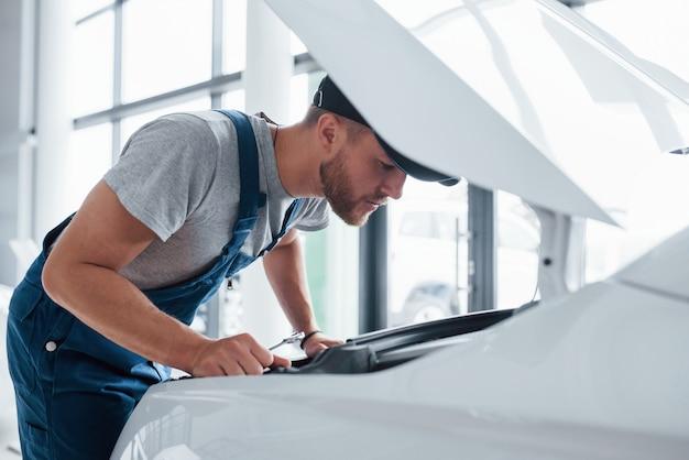 Controleren of details in orde zijn. man in blauw uniform en zwarte hoed beschadigde auto repareren