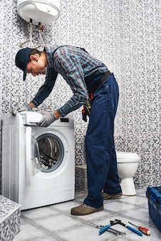 Controleren van wasmachine werk werkende man loodgieter in badkamer