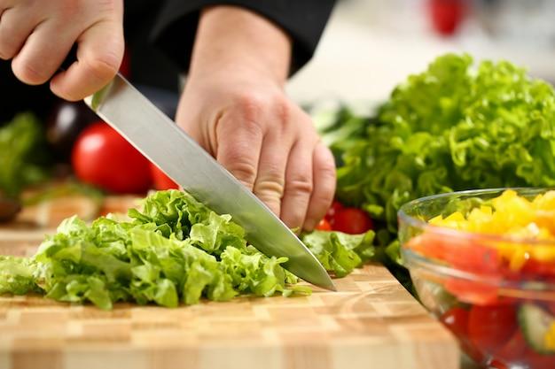 Cook houdt mes in de hand en snijdt door