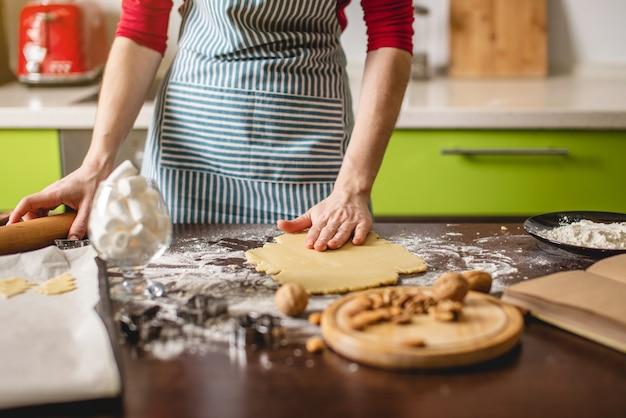 Cook huisvrouw koekjes thuis maken op een kleurrijke keuken