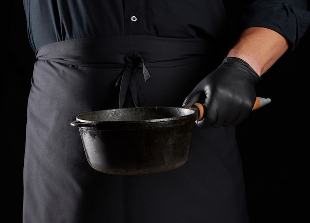 Cook in zwart uniform en latex handschoenen houdt een lege ronde vintage zwarte gietijzeren pan voor hem, low key