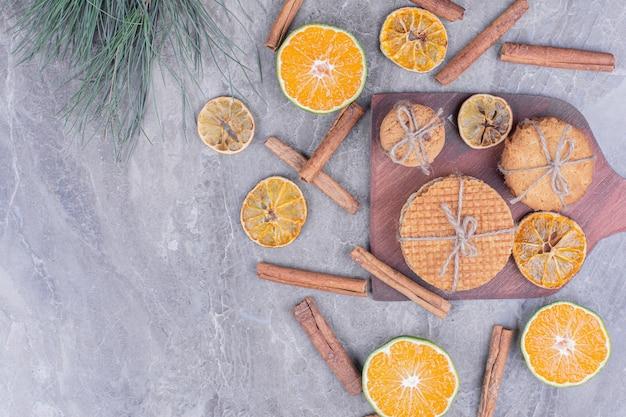Cookie-variëteiten op een houten bord met kaneel en sinaasappels