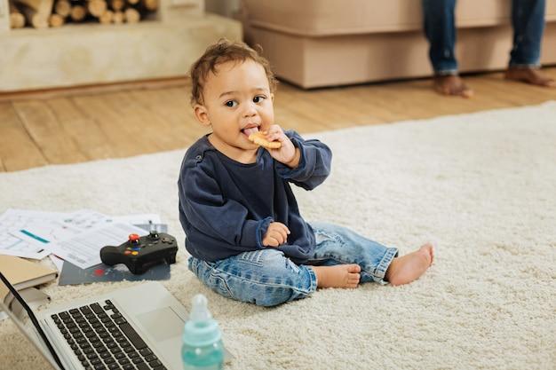 Cookies hebben. mooie gelukkige krullende kleine jongen die met zijn speelgoed speelt en koekjes eet terwijl hij op de vloer zit
