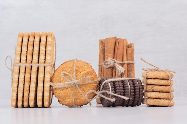 Cookies in touw met kaneelstokjes op witte tafel.