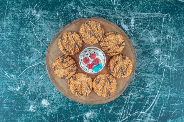 Cookies rondom een cupcake op een houten bord op blauwe achtergrond. hoge kwaliteit foto