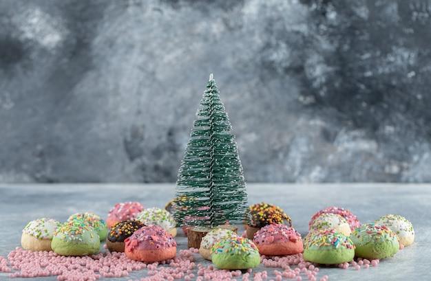 Cookies versierd met hagelslag rond dennenboom.