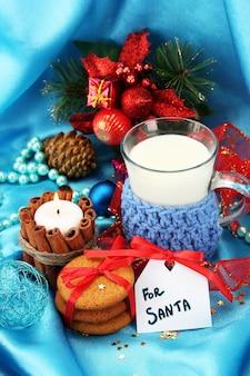 Cookies voor de kerstman: conceptueel beeld van gemberkoekjes, melk en kerstversiering op blauwe achtergrond
