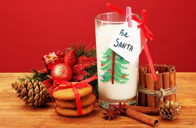 Cookies voor de kerstman: conceptuele afbeelding van gemberkoekjes, melk en kerstversiering op rood