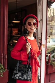 Cool aantrekkelijke brunette vrouw in stijlvolle rode jurk, trendy heldere baret en zonnebril opent leren zwarte handtas en opent cafédeur