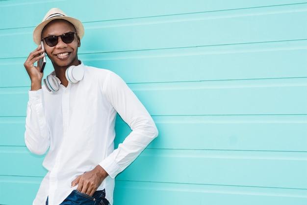 Cool afro-amerikaans mannetje dat iemand belt via zijn telefoon tegen een lichtblauwe achtergrond Gratis Foto