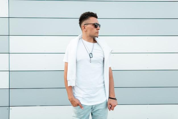 Cool amerikaanse jongeman hipster in zonnebril in trendy blauwe spijkerbroek in een modieus wit t-shirt is poses in de stad