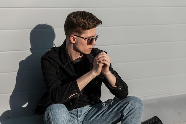 Cool amerikaanse jongeman in modieuze zonnebril in stijlvolle casual denim kleding