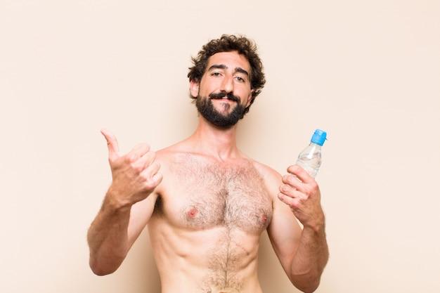 Cool bebaarde jongeman met een fles water