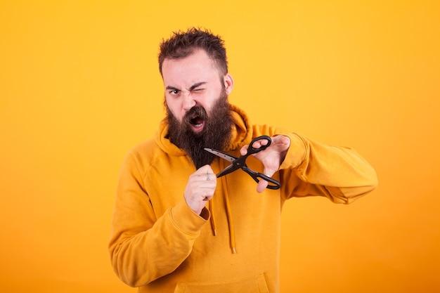 Cool bebaarde man die doodsbang kijkt terwijl hij zijn baard over een gele achtergrond knipt. macho-man. levensstijl
