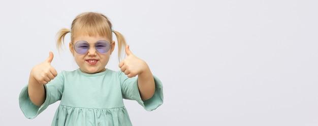 Cool blond haar blonde jongen meisje in moderne mode groene jurk en zonnebril vertoont duimen omhoog teken gebaar met beide handen