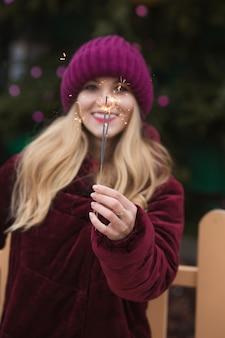 Cool blond model met gloeiende bengaalse lichten bij de belangrijkste kerstboom in kiev. vervagingseffect