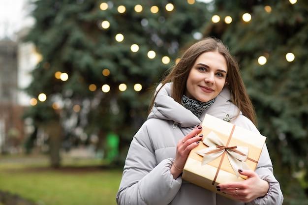 Cool blonde vrouw met een geschenkdoos op straat. lege ruimte