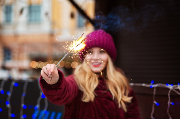 Cool blonde vrouw met gloeiende sterretjes bij de kerstboom. vervagingseffect