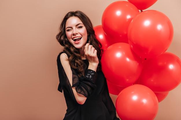 Cool brunette meisje in elegante blouse houdt heldere ballonnen en knipoogt op geïsoleerde achtergrond.