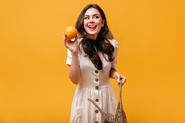Cool brunette meisje in katoenen jurk met strik om haar nek houdt sinaasappel en likken.