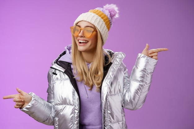 Cool brutaal vriendelijk ogend blond meisje wijzend verschillende kanten rechts links kies welke kant gaan kijken verrukt zorgeloos genieten van geweldige wintervakantie draag stijlvolle zilveren jas, hoed zonnebril.
