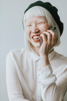 Cool en stijlvol albino-meisje dat op haar telefoon praat