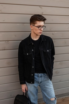 Cool fashion jonge man in bril met kapsel in stijlvolle casual denim kleding met vintage lederen zwarte rugzak