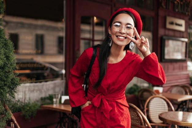Cool gebruinde aziatische vrouw in rode jurk en stijlvolle baret toont vredesteken