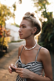Cool gelooide jonge blonde vrouw met haar broodje gekleed in gestreepte jurk wegkijken en lopen in het park