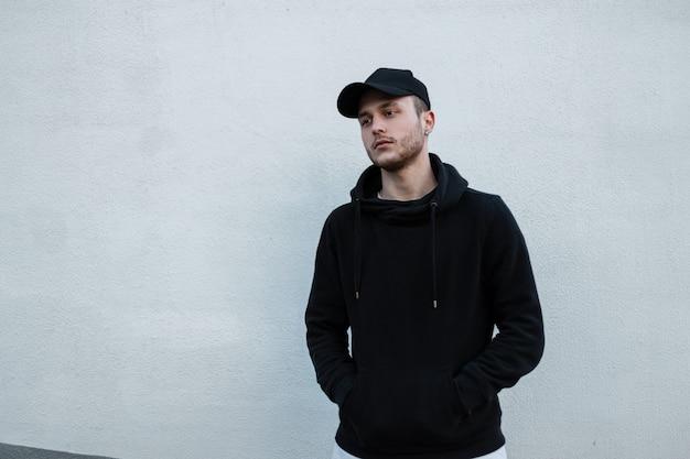 Cool hipster man in fashion zwarte pet en stijlvolle zwarte hoodie staat in de buurt van witte muur op straat. mannelijke stedelijke casual stijl