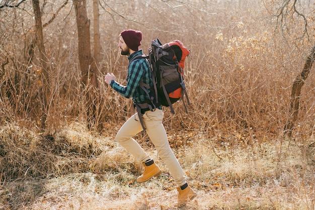 Cool hipster man reizen met rugzak in herfst bos met geruit hemd en hoed