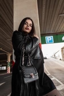 Cool hipster meisje met mode zonnebril in modieuze zwarte kleding met leren jas met een stijlvolle handtas op straat