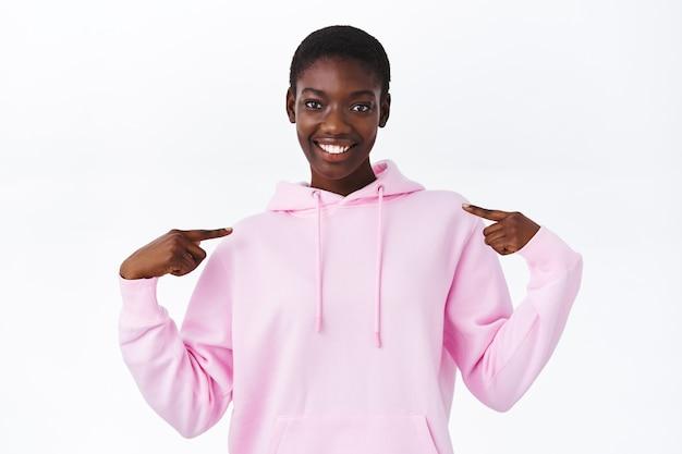 Cool jong afrikaans-amerikaans meisje met kort haar dat naar zichzelf wijst en glimlacht, opschepperig praat over eigen prestatie, introduceren