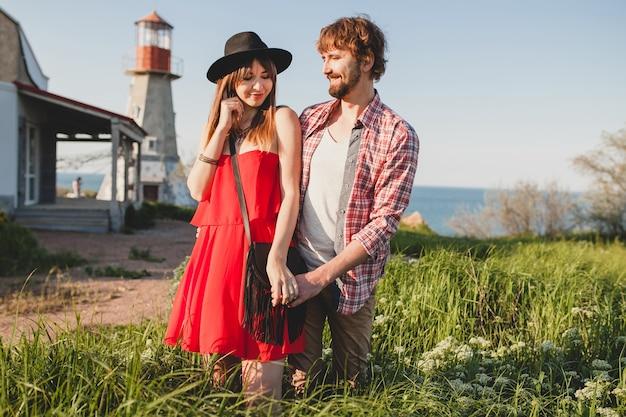 Cool jong stijlvol paar verliefd op platteland, indie hipster bohemien stijl, weekendvakantie, zomer outfit, rode jurk, groen gras, hand in hand, glimlachen