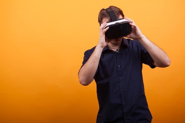 Cool jonge man experimenteren vr in blauw shirt over gele achtergrond. op zoek naar visie