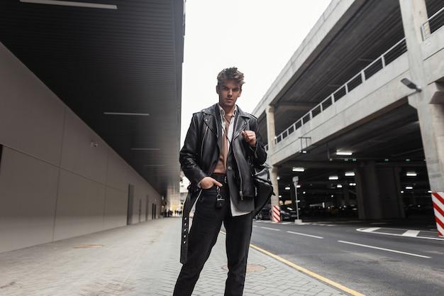 Cool jonge man in oversized leren jas in vintage jeans in lente laarzen met een modieuze zwarte rugzak loopt op straat in de buurt van de parkeerplaats. amerikaanse man in trendy kleding buitenshuis. vrijetijdskleding.