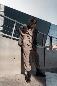 Cool jonge man model met vintage zonnebril in mode grijze blazer, shirt, broek en zwarte laarzen staat op stedelijke achtergrond bij zonlicht. zakelijke casual stijl